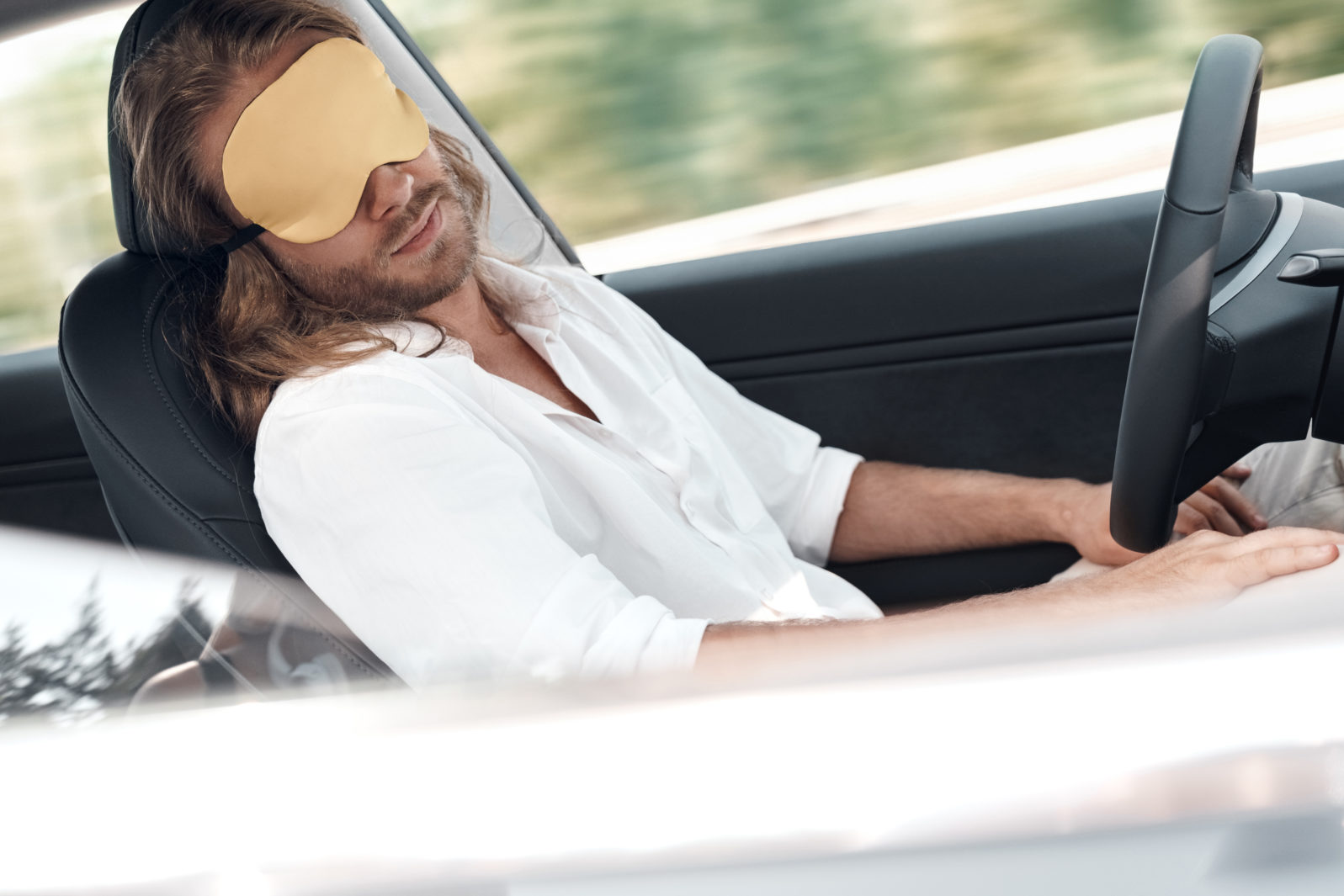 Tired man sitting in car, wearing in sleeping mask