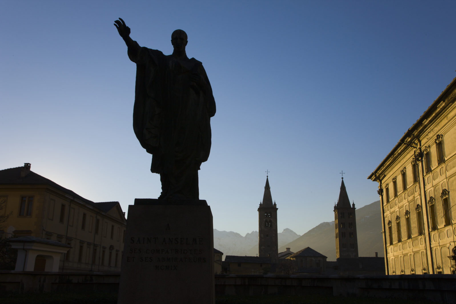 Statue of Saint Anselm and the towers of the Cathedral of Aosta, the Cattedrale di Aosta de Corso Pere-Laurent in Aosta. Aosta Valley. Italy. Europe
